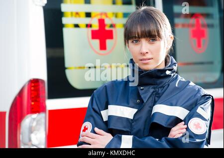 Portrait of a male paramedic, ambulance in the background - Stock Photo