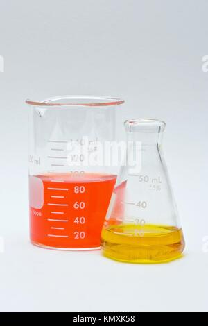 Flask and beaker with colorful liquids as pH indicators on a white background - Stock Photo