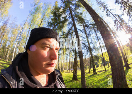 forester in black clothes going through the forest - Stock Photo