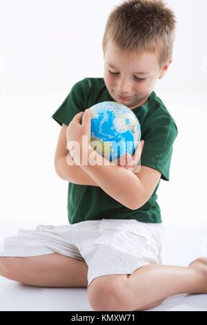 Little boy embracing the globe to protect it - Stock Photo