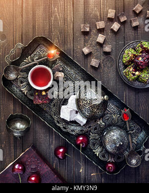 Tea with Turkish delights rahat lokum and cherry on wooden table in magic colors with space for your text - Stock Photo
