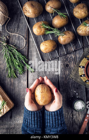 Woman cooking potato with rosemary on rustic wooden background in the kitchen - Stock Photo