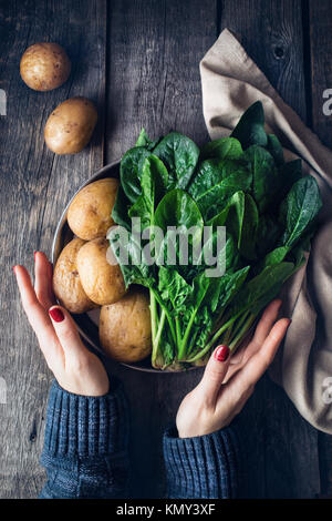 Woman holding plate with potatoes and fresh spinach on rustic wooden background in the kitchen - Stock Photo