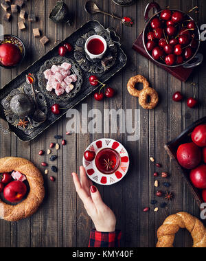 Woman touching red tea near Turkish delights rahat lokum, simits and fruits on wooden table - Stock Photo
