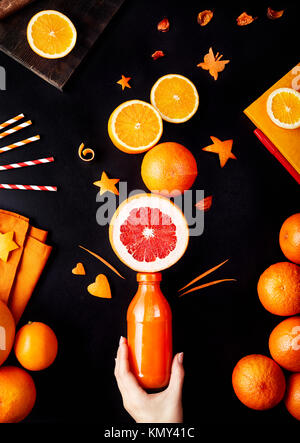 Fresh detox juice from oranges, grapefruit and lemon on black background flay lay - Stock Photo