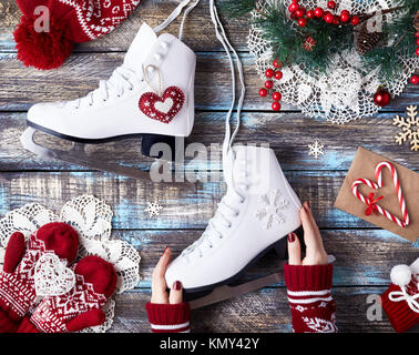 Girl in red sweater holding white skates on wooden blue table on winter holidays - Stock Photo
