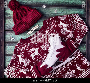 Red sweater holding white skates on wooden green background at winter holidays - Stock Photo
