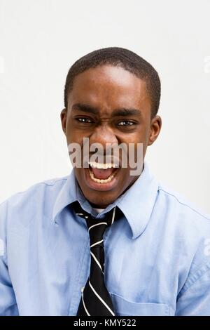 Dark skinned young business professional screaming, MBA student, or such, isolated on white - Stock Photo