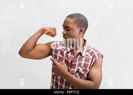 Young dark skinned handsome guy proudly pointing at his biceps showing how strong he is wearing a checkered shirt, - Stock Photo