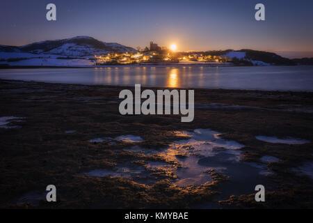 Moonset over Nanclares de Ganboa village in a frozen morning - Stock Photo