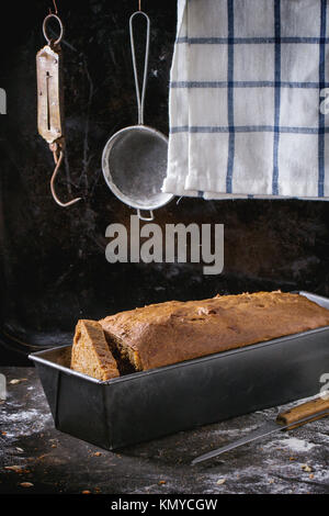 Homemade rye bread in bread pan over kitchen table with towel and vintage stainer and steelyard at background - Stock Photo