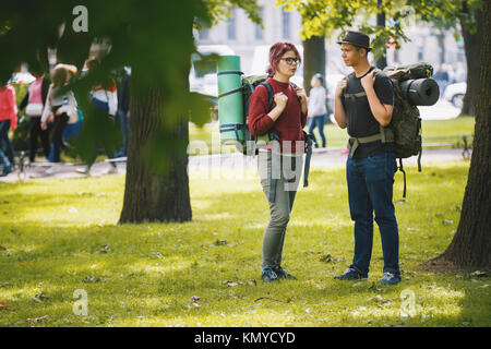 Teenagers tourists with backpacks have conversation in the park at summer midday - Stock Photo