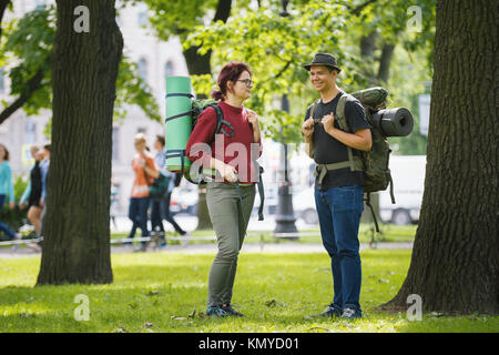 Teenagers tourists with backpacks standing in the park at summer midday - Stock Photo