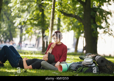 Couple of teenagers tourists with backpacks have rest in the city park - Stock Photo
