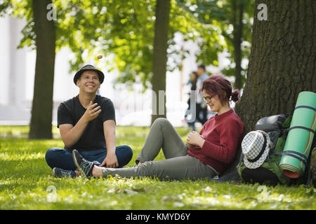 Young couple tourists with backpacks have rest in the park - Stock Photo