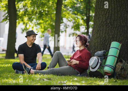 Teenagers tourists with backpacks in the park at summer midday - Stock Photo