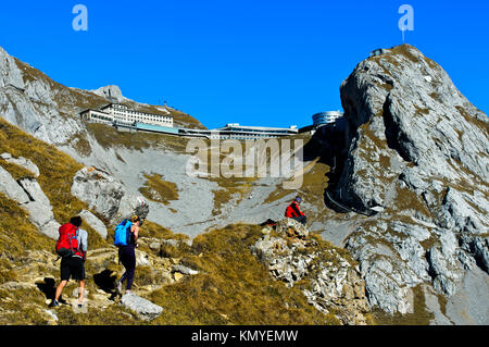 Hikers in the Pilatus massif, behind hotels Pilatus Kulm and Pilatus Bellevue, peak Esel, Alpnachstad, Switzerland - Stock Photo