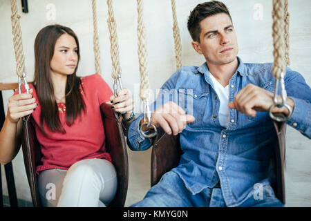 Portrait of couple sitting in swings - Stock Photo