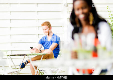 Handsome happy man holding phone in a cafe while sitting at a ta - Stock Photo