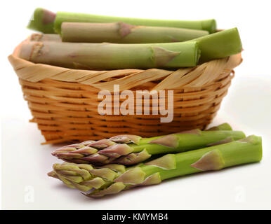 Fresh asparagus in a basket over white background - Stock Photo