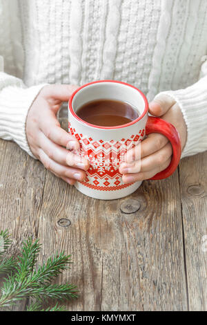 Female hands holding red mug of hot chocolate (coffee, tea, cacao) on rustic wooden background with copy space. - Stock Photo