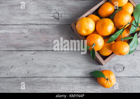 Tangerines (oranges, clementines, citrus fruits) with green leaves over wooden background with copy space - Stock Photo