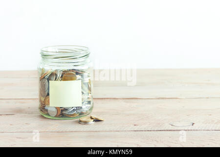 Coins in glass jar with empty label. Money savings concept. Jar with assorted coins with label for text on wooden - Stock Photo