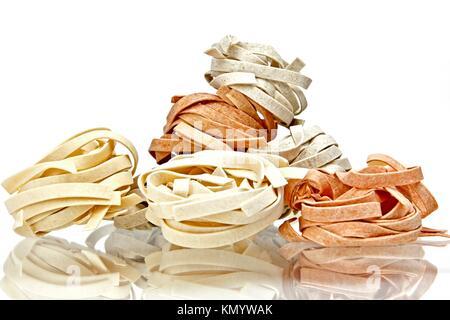 Tagliatelle pasta in three colors on white background - Stock Photo