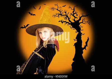 Halloween beautiful girl in dried tree and bat orange background - Stock Photo