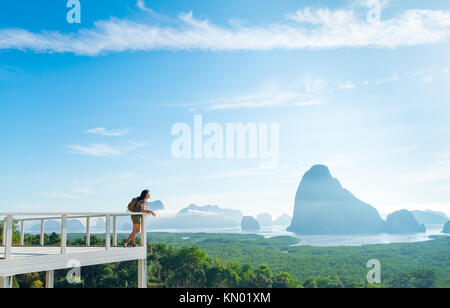 Happy young traveler woman backpacker chill out and enjoying a beautiful sky of nature at mountain panorama view - Stock Photo