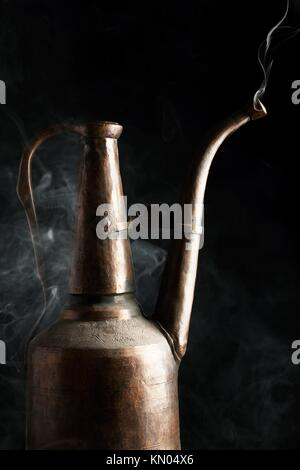 Oriental vintage boiling brass pot with vapor against black backgrounds - Stock Photo