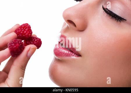 Beautiful woman eating sweet raspberries - Stock Photo