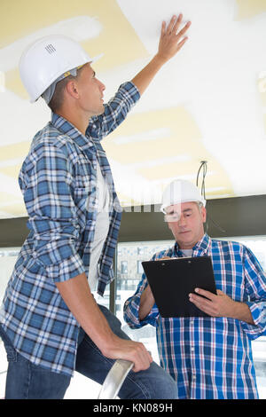 construction manager inspecting the ceiling plaster - Stock Photo