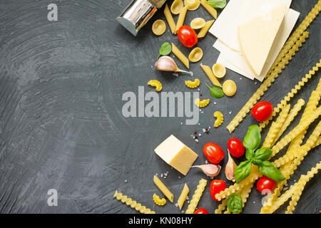 Italian foods concept and menu design. Mix of pasta, cheese, spices, tomatoes and basil on a gray slate background. - Stock Photo