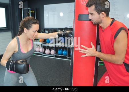 young beautiful woman boxer kicking a punching bag - Stock Photo