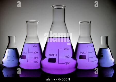 five vials of purple liquid conical laboratory on a white background - Stock Photo