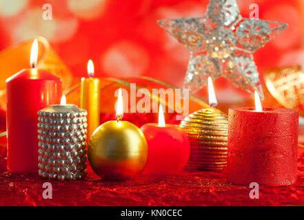 Christmas card candles red and golden in a row on blurred background - Stock Photo