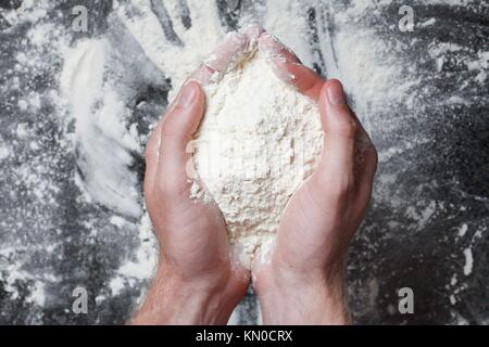 Hands holding white wheat flour - Stock Photo