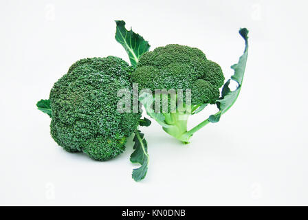 Two fresh inflorescences of broccoli isolated on white background - Stock Photo
