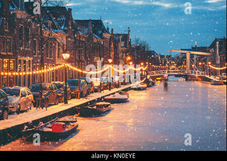 Winter scene in Alkmaar Netherlands with natural ice and falling snow - Stock Photo