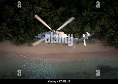 A U.S. Navy MH-60S Seahawk helicopter flies over the beach during a patrol flight November 28, 2017 in Guam.  (photo - Stock Photo