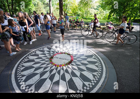 NEW YORK CITY - AUGUST 21, 2017: Tourists gather around the John Lennon Imagine memorial at Strawberry Fields in Central Park.