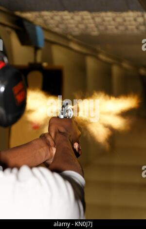 A picture taken over the shoulder of a young man firing a gun at a shooting range in the precise moment of the muzzle - Stock Photo