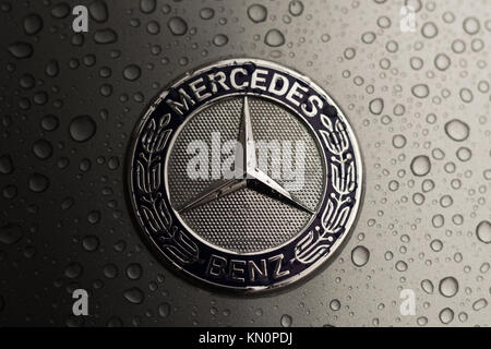 Kiev, Ukraine - 03 NOVEMBER, 2017: Close-up emblem of modern luxury Mercedes-Benz car with grey wet hood. - Stock Photo