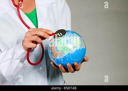 Female doctor listening to the Earth with stethoscope - Stock Photo