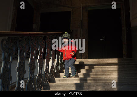 little boy down the stairs. He goes for a walk on the street. - Stock Photo