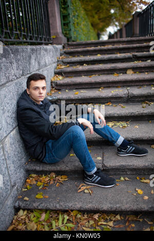 A young guy sitting on the stairs in the Park among the yellow leaves. - Stock Photo