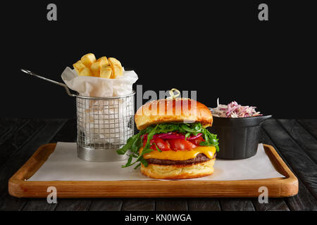 Juicy beef burger with lingonberry sauce, melted cheese, arugula served with fried potato and red cabbage - Stock Photo