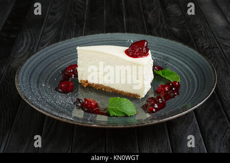 Piece of cheese cake decorated with cherry, strawberry and raspberry - Stock Photo