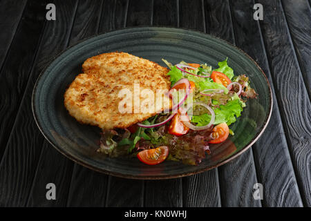 schnitzel in breading with fresh vegetables and rings of red onion - Stock Photo